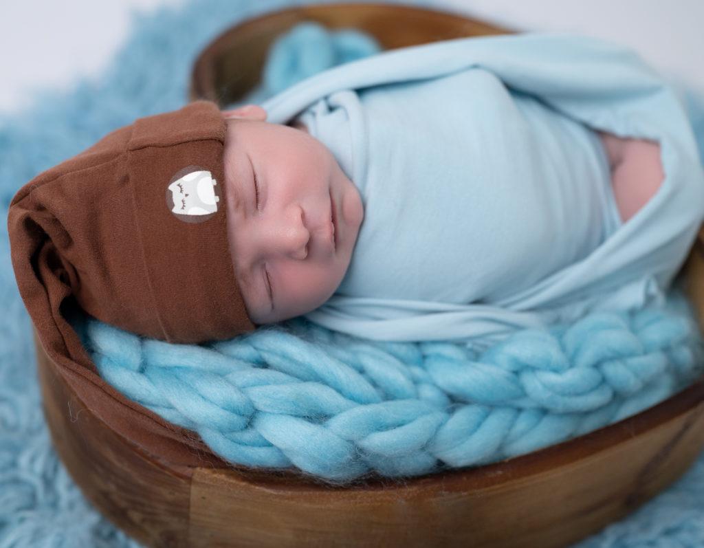 nouveau-né emmailloté de bleu bonnet de lutin marron endormi dans un coeur en bois sur une tresse en laine bleue photographe naissance nouveau-né Houilles Yvelines la Défense