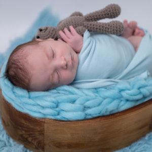 nouveau-né emmailloté de bleu endormi dans un coeur en bois sur une tresse en laine bleue tenant un petit nounours dans ses mains photographe naissance nouveau-né Houilles Yvelines la Défense
