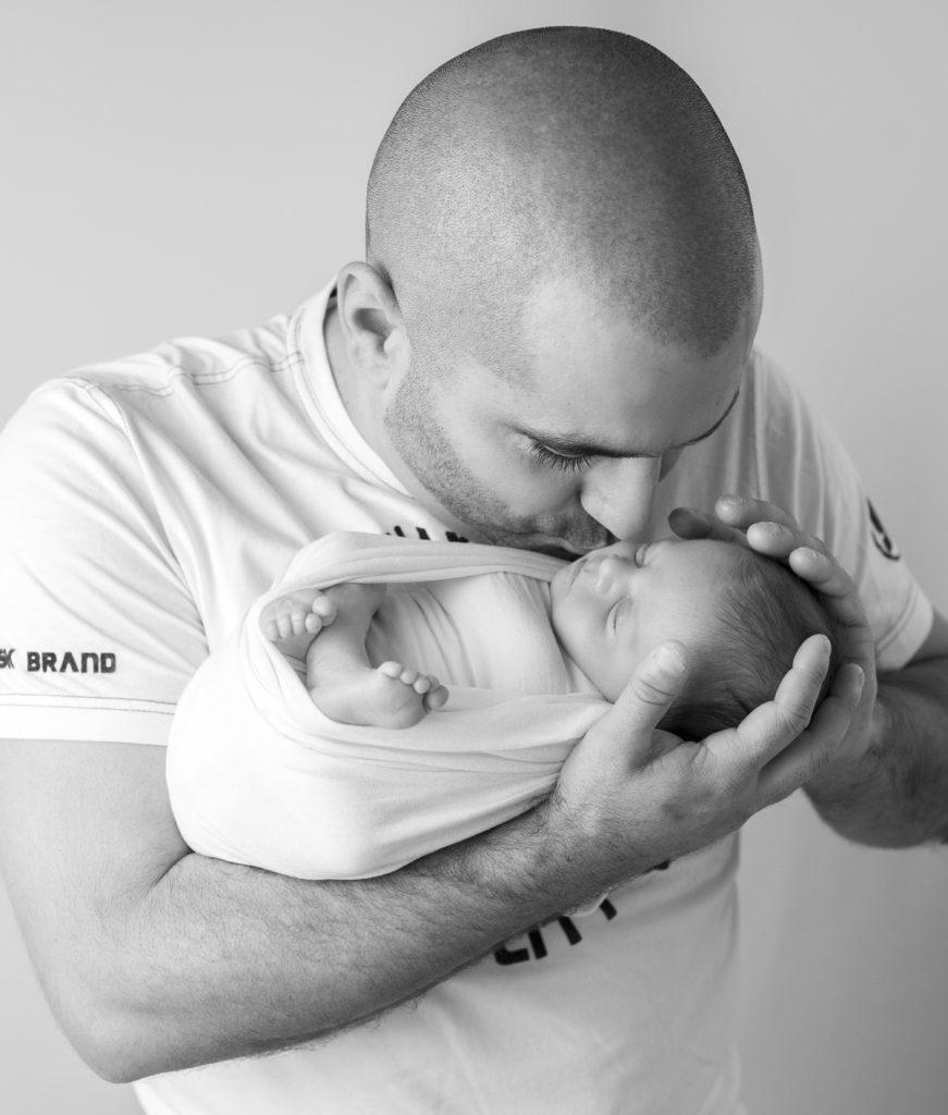 Jeune papa qui tient son nouveau-né emmailloté dans ses bras. Photographie en noir et blanc. Photographe naissance nouveau-né Houilles Yvelines la Défense