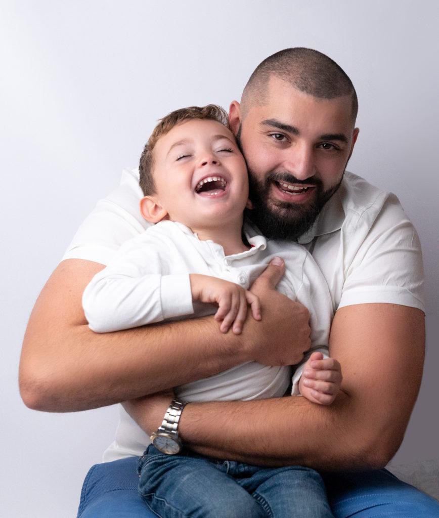 jeune papa rit avec son petit garçon de trois ans qui rit aux éclats photographe famille Houilles Yvelines la Défense