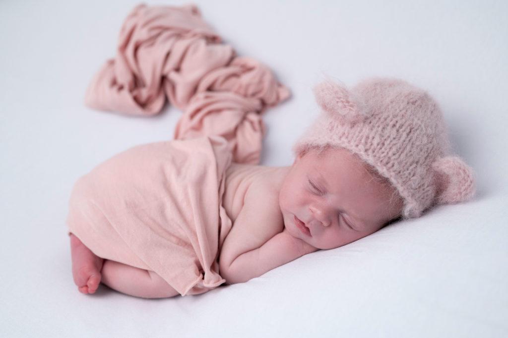 nouveau-né bonnet doudou rose et wrap rose allongée en pose bump up sur beanbag. Photographe naissance nouveau-né Houilles Yvelines la Défense