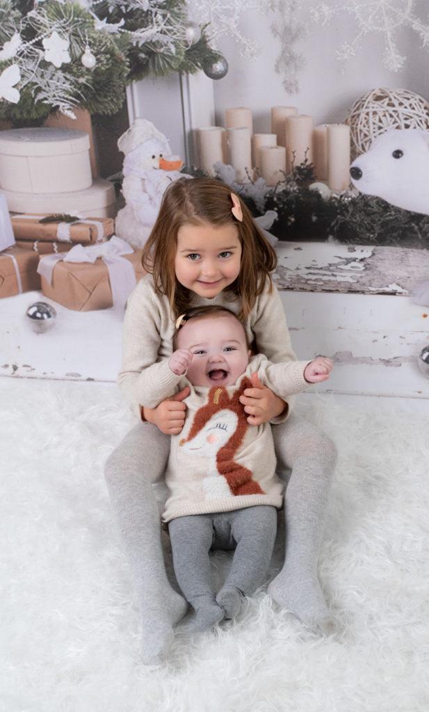 deux soeurs assises ensemble sur fond de Noël photographe bébé famille Houilles Yvelines la Défense