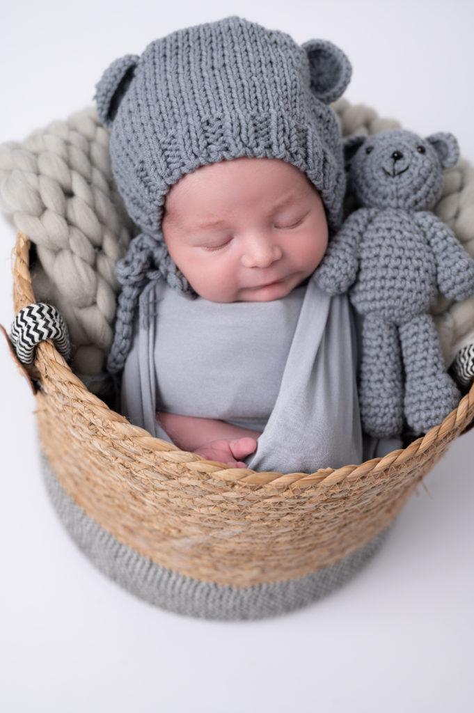 nouveau-né emmailloté de gris endormi dans un panier en osier photographe naissance nouveau-né bébé Houilles Yvelines la Défense