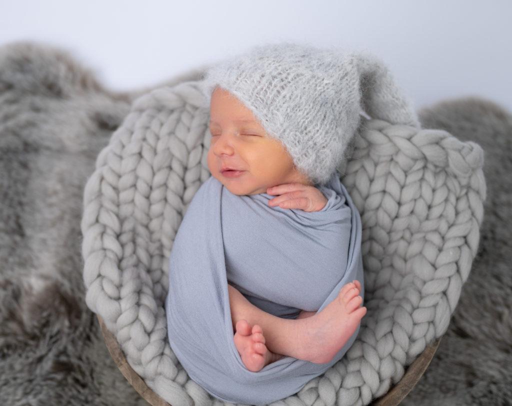 nouveau-né bonnet d'elfe emmailloté de gris qui sourit aux anges photographe naissance nouveau-né Houilles Yvelines la Défense