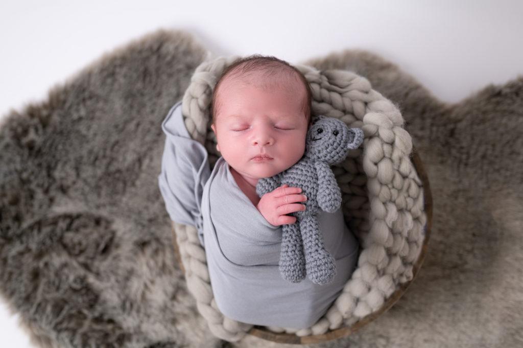 nouveau-né emmailloté de gris endormi dans un panier sur tresse en laine grise en tenant un nounours dans ses mains photographe naissance nouveau-né Houilles Yvelines la Défense