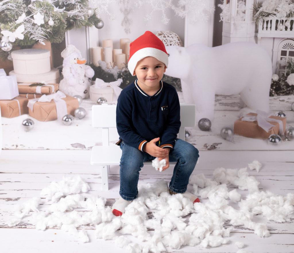 Petit garçon de trois ans assis sur un mini banc blanc sur fond de Noël neige en coton photographe enfant famille Houilles Yvelines la Défense