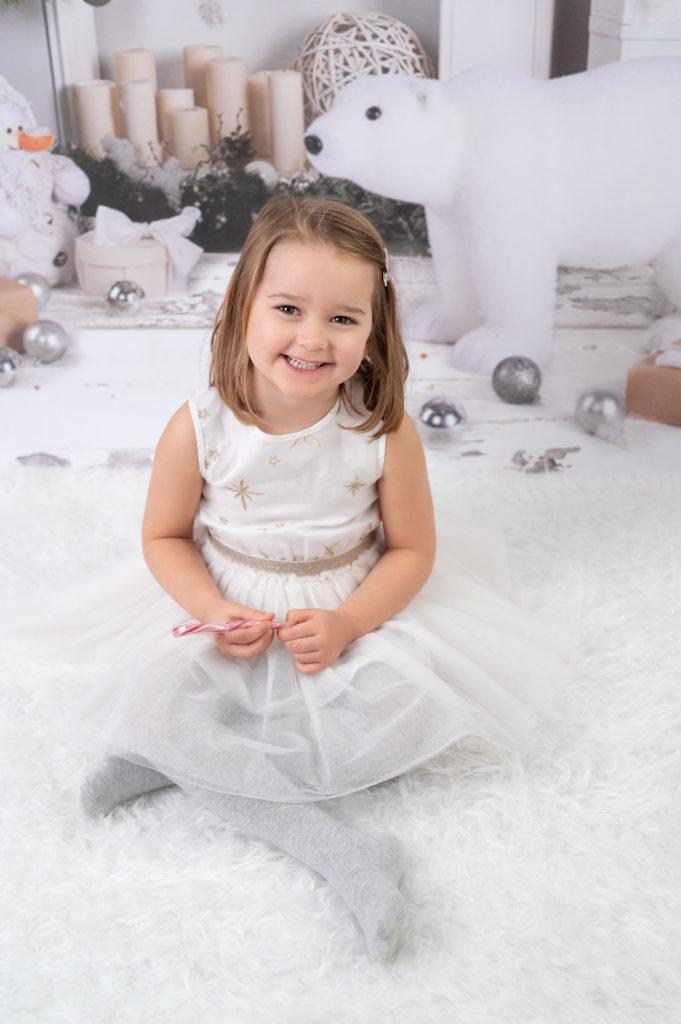 Petite fille robe de princesse assise sur tapis blanc sur fond de Noël photographe enfant Houilles Yvelines la Défense