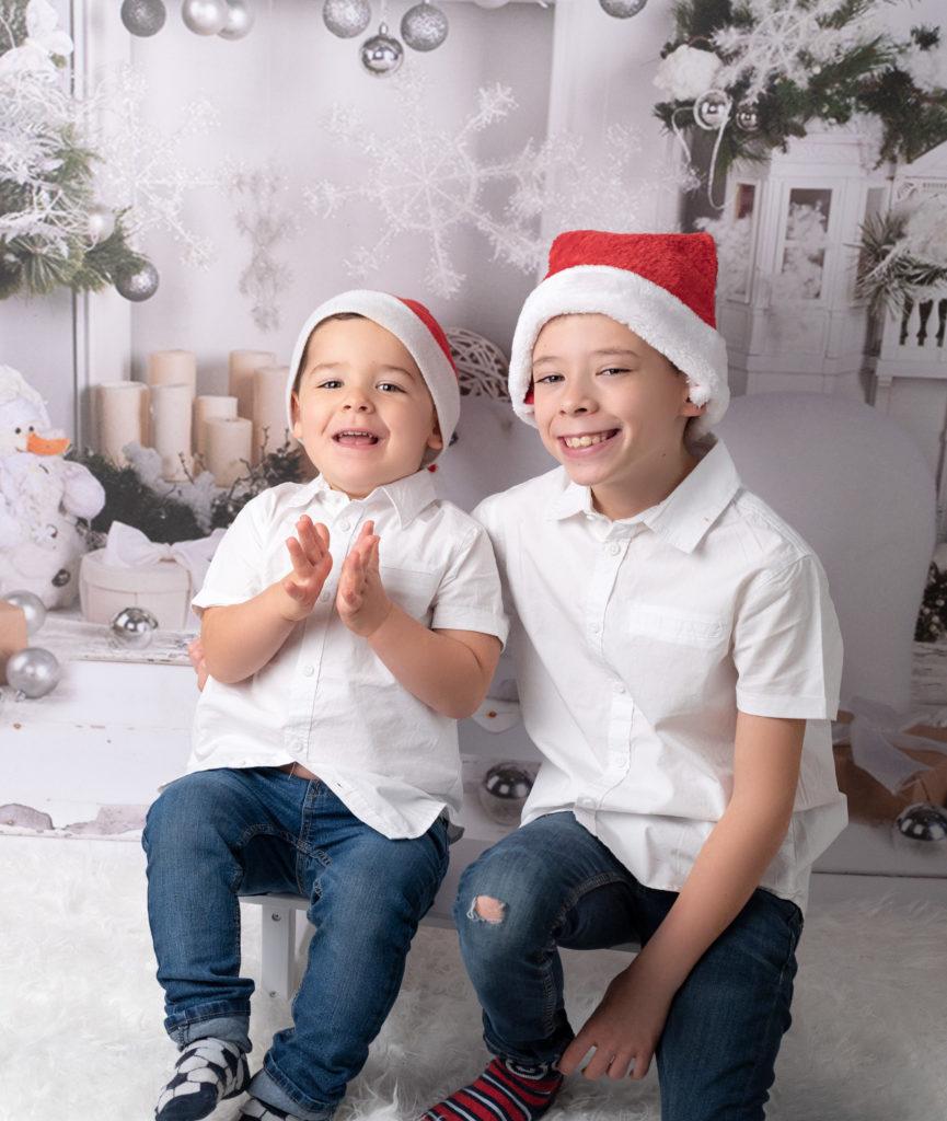 Petits garçons assis sur un banc blanc sur fond de Noël photographe enfants famille Houilles Yvelines la Défense