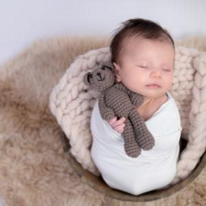 nouveau-né endormi dans une terrine ronde tenant un nounours photographe naissance nouveau-né Houilles Yvelines la Défense