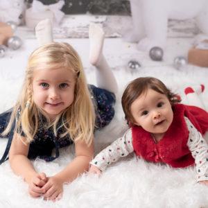 Petites filles de 4 anas et 6 mois allongées côte à côte à plat ventre dans un décor de Noël photographe bébé enfant famille Houilles Yvelines la Défense