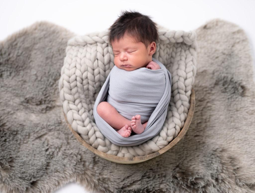 nouveau-né emmailloté de gris sur couverture en mailles grise photographe naissance nouveau-né bébé Houilles Yvelines la Défense
