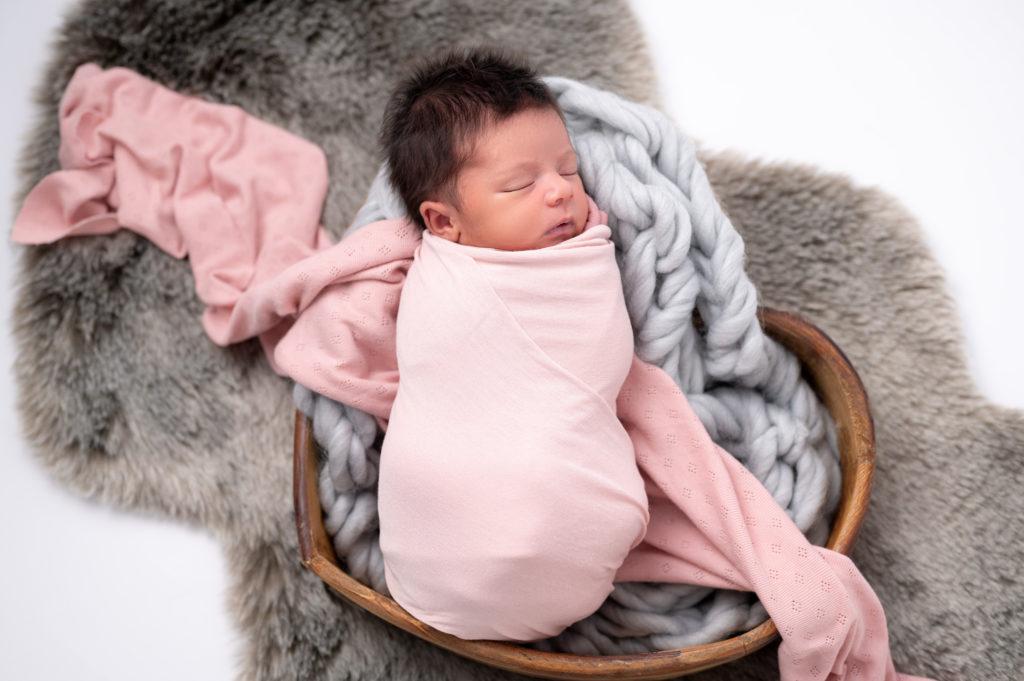 nouvelle-née emmaillotée de rose sur tresse en laine grise dans contenant en bois photographe naissance nouveau-né Houilles Yvelines la Défense