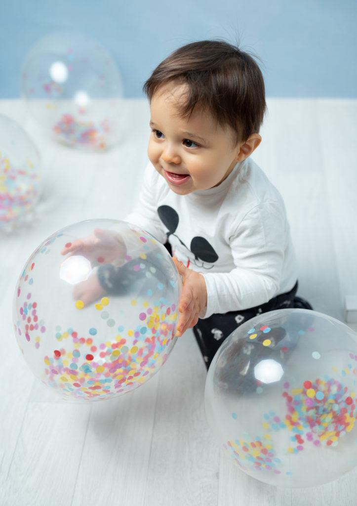 grand bébé de un an qui joue avec des ballons confettis photographe bébé Houilles Yvelines la Défense