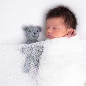 Nouveau-né emmailloté de blanc endormi avec une couverture en dentelle et un nounours gris photographe naissance nouveau-né Houilles Yvelines la Défense