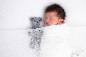 nouveau-né emmailloté endormi sur posing bag avec couverture en dentelle photographe naissance nouveau-né Houilles Yvelines la Défense