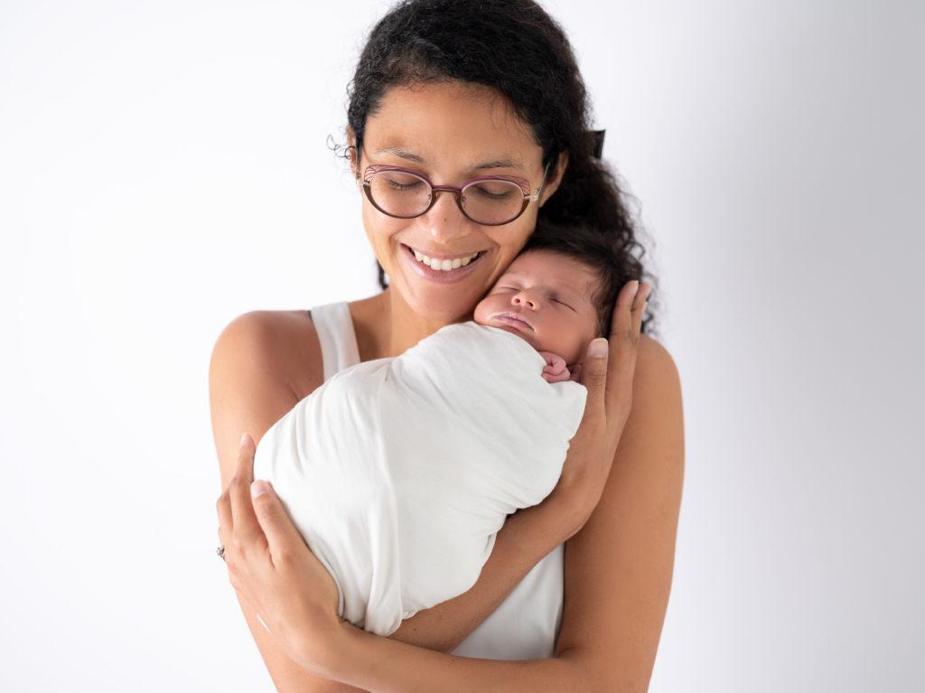 jeune maman tenant sa nouvelle-née dans les bras photographe naissance Houilles Yvelines la Défense