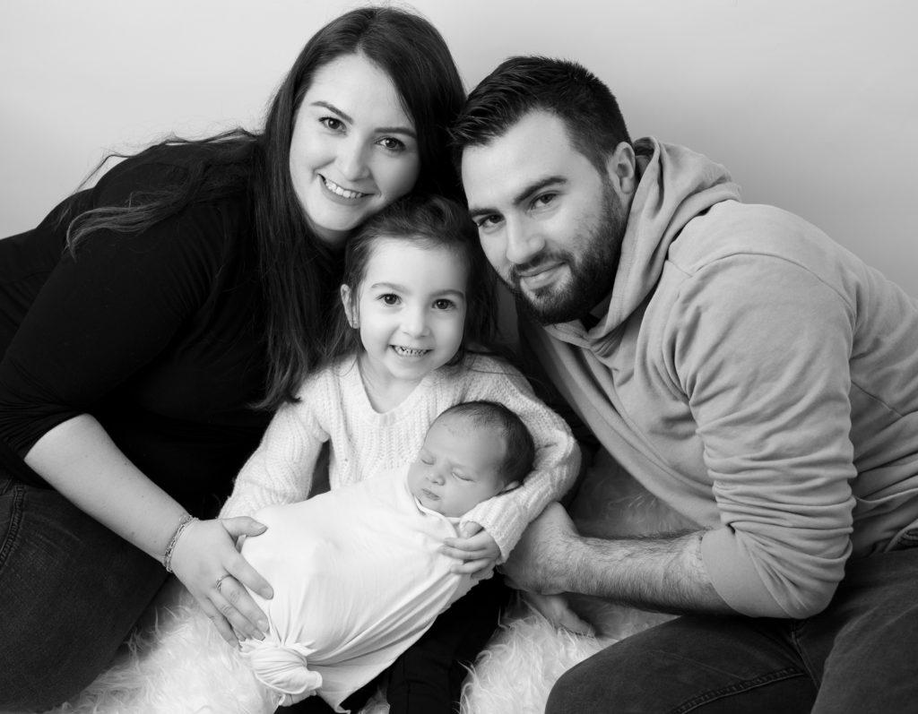 Portrait noir et blanc d'une famille avec les parents entourant leur petite fille de trois ans qui tient son petit frère nouveau-né dans les bras photographe bébé enfant famille Houilles Yvelines la Défense