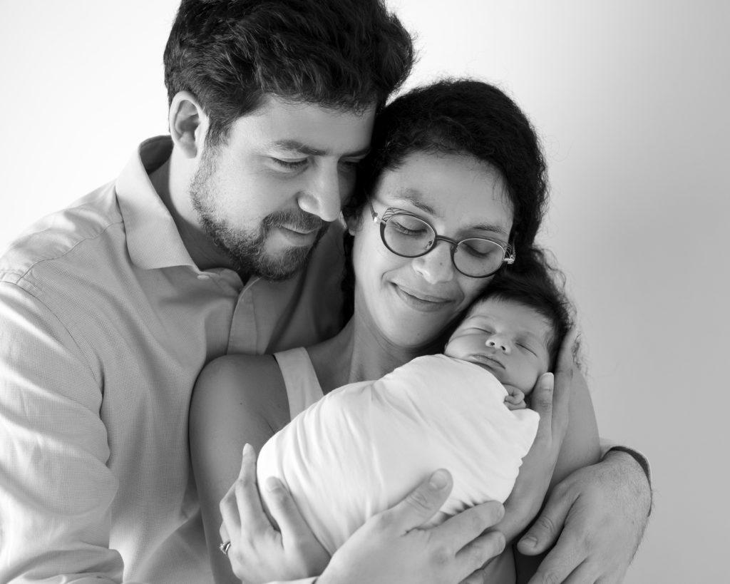 Portrait noir et blanc de jeunes parents tenant leur nouveau-né dans les bras photographe famille naissance Houilles Yvelines la Défense