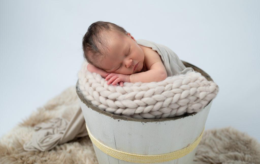 bébé endormie dans seau en bois photographe naissance nouveau-né houilles yvelines la défense