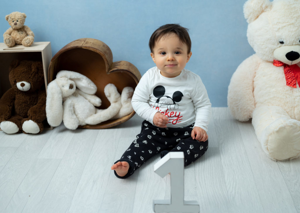 bébé de un an assis sur fond bleu avec peluches et nounours photographe grand bébé Houilles Yvelines la Défense