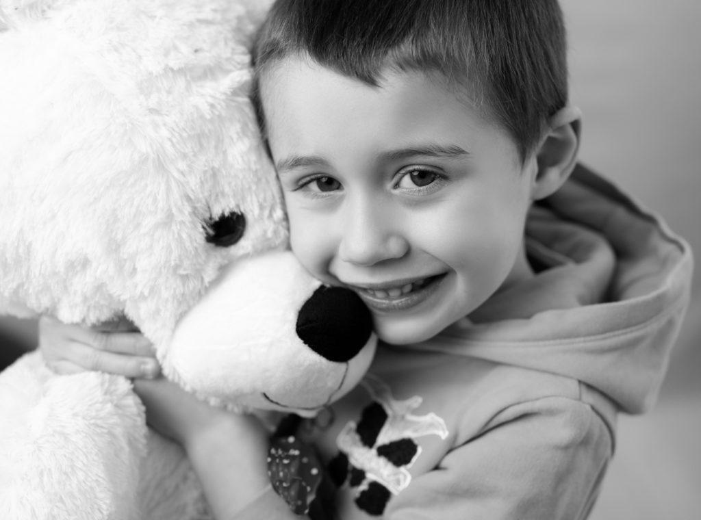 portrait noir et blanc d'un petit garçon qui tient un gros nounours contre lui photographe enfant Houilles Yvelines la Défense