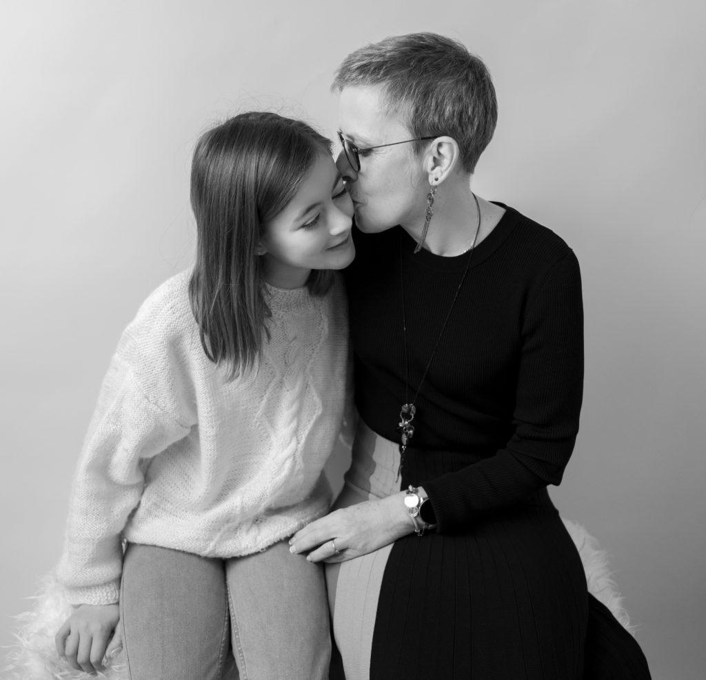 Portrait noir et blanc d'une grand-mère embrassant sa petite-fille photographe famille Houilles Yvelines la Défense