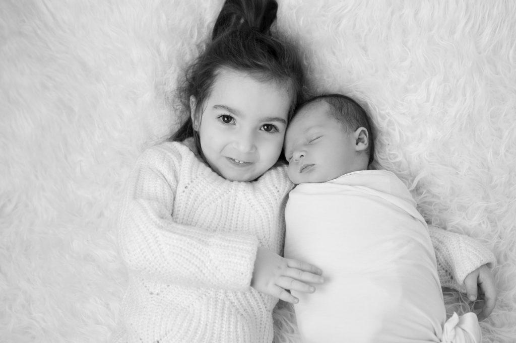 petite fille tenant son tout-petit frère dans ses bras photographe famille naissance Houilles Yvelines la Défense