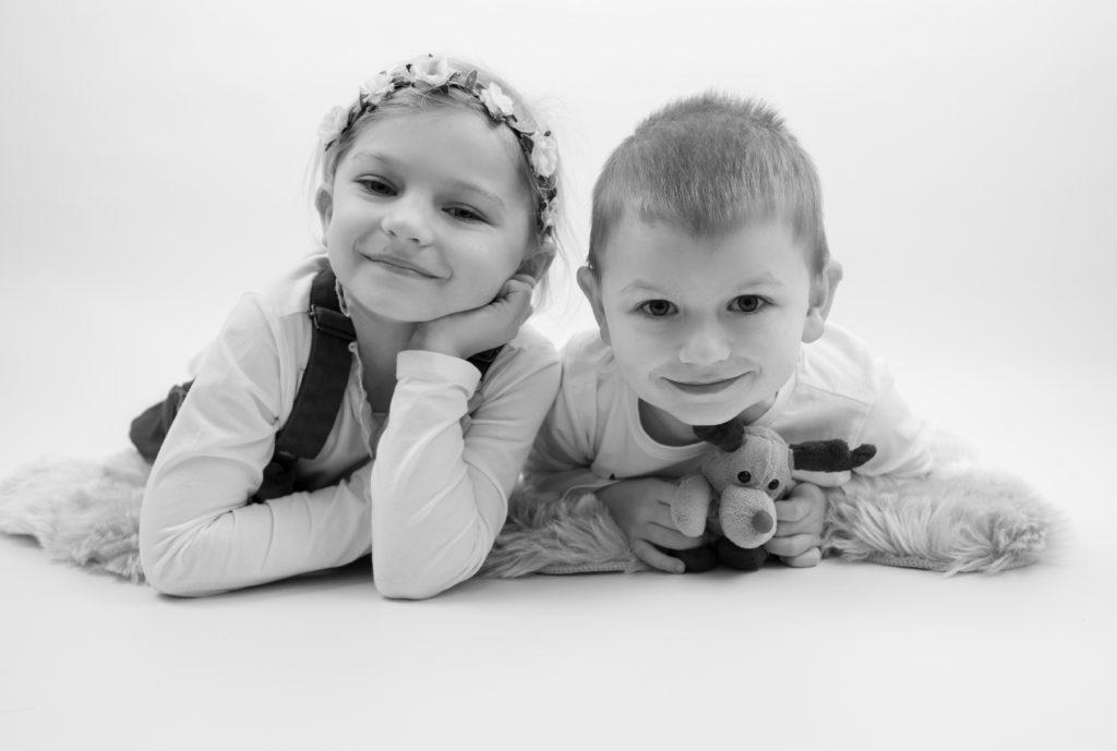 portrait noir et blanc d'enfants allongés à plat ventre sur tapis de fourrure photographe enfants Houilles Yvelines la Défense