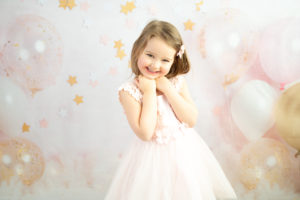 Petite fille sur fond ballons et étoiles roses et dorés photographe enfant anniversaire Houilles Yvelines la Défense