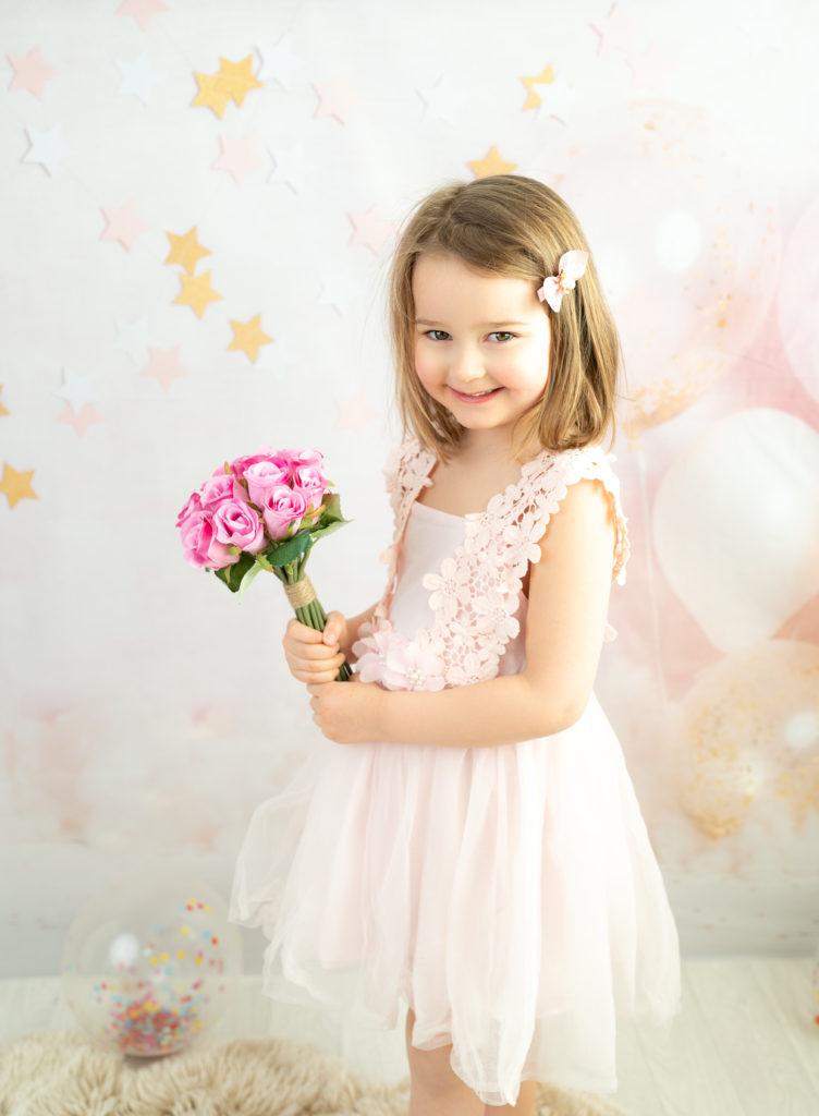 Petite fille de cinq ans sur fond ballons et étoiles tient un bouquet de fleurs photographe enfant anniversaire Houilles Yvelines la Défense