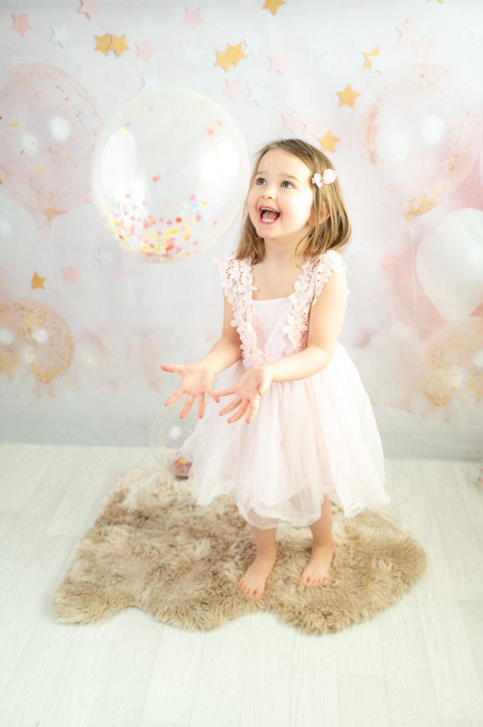 Petite fille sur fond ballons et étoiles joue avec un ballon confettis photographe enfant anniversaire Houilles Yvelines la Défense