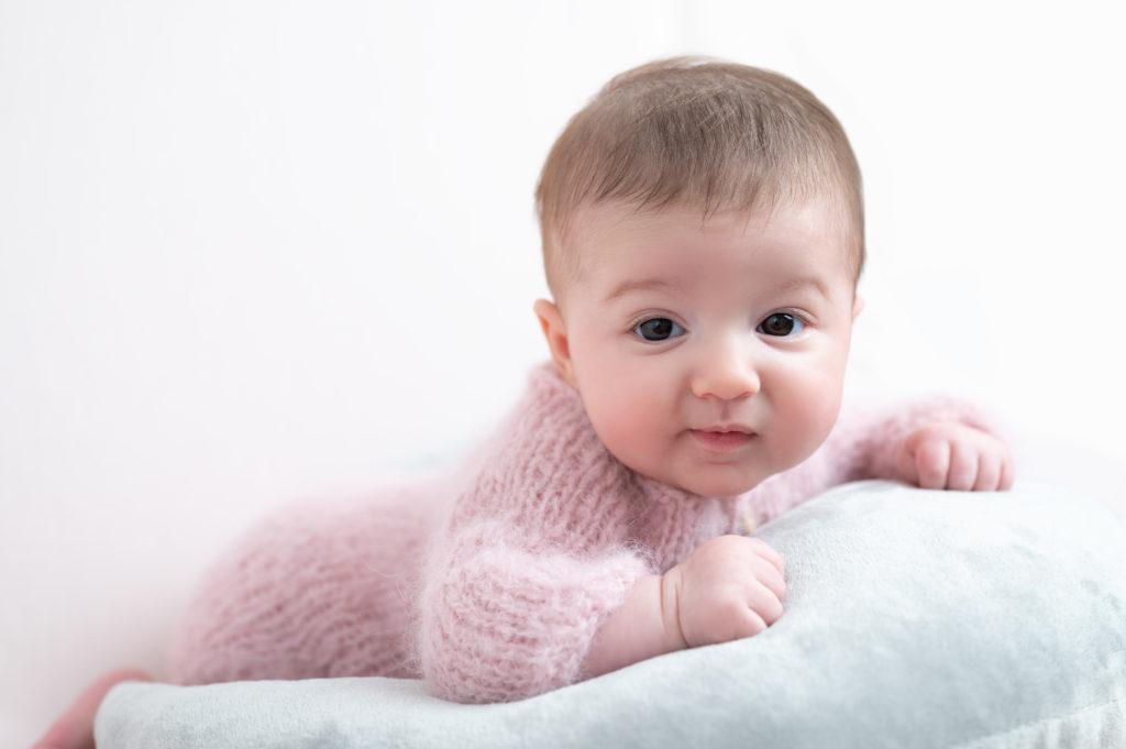 bébé de trois mois body rose laine doudou à plat ventre sur posing bag photographe bébé Houilles la Défense