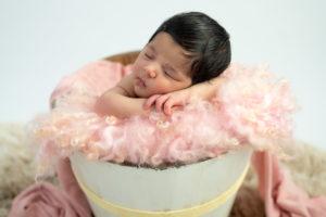 nouveau-né de 12 jours endormie dans seau en bois sur tapis bouclé rose photographe naissance nouveau-né Houilles Yvelines la Défense