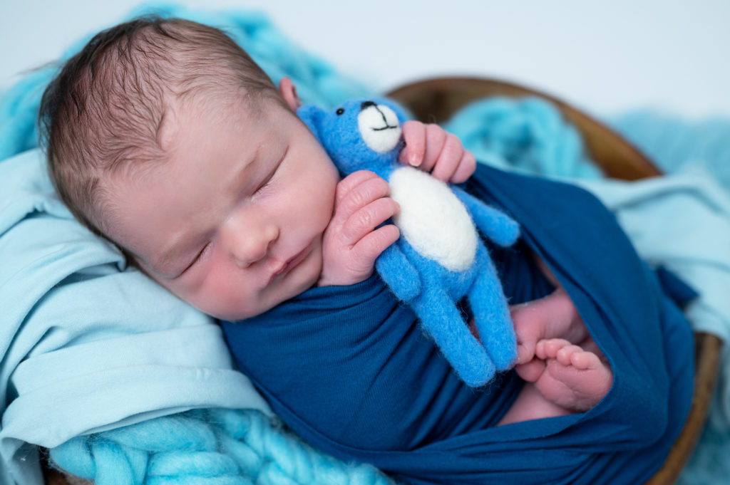 Nouveau-né emmailloté de bleu pétrole tenant dans ses mains un petit nounours bleu photographe naissance nouveau-né Houilles Yvelines la Défense