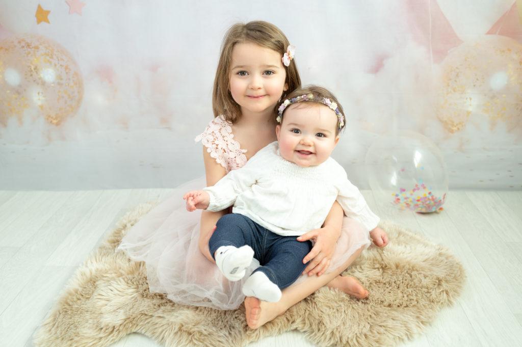 petite fille de cinq ans et sa petite soeur de cinq mois assise sur un décor ballons et étoiles photographe enfant bébé Houilles Yvelines la Défense