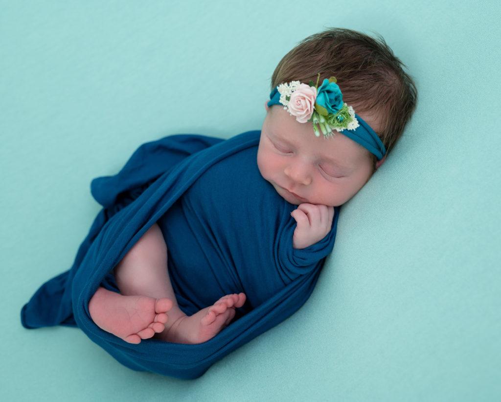 nouvelle-née headband et wrap bleu pétrole endormie sur posing bag vert menthe photographe naissance nouveau-né houilles la Défense