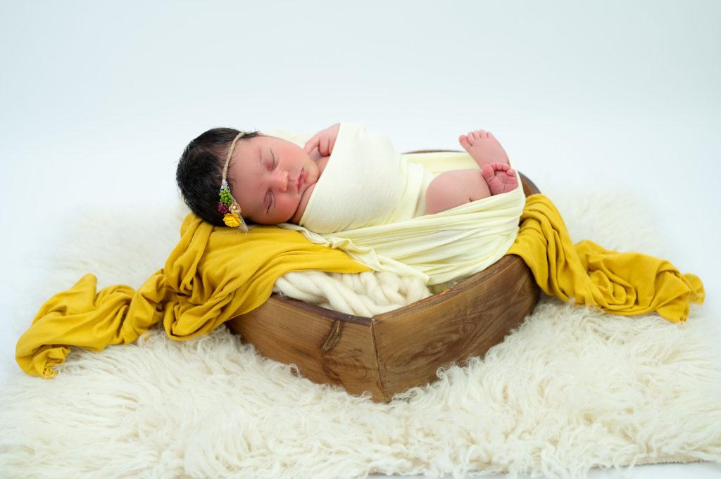 nouvelle née emmaillotée de jaune pâle sur wrap jaune moutarde dans coeur en bois photographe naissance nouveau-né Houilles Yvelines la Défense