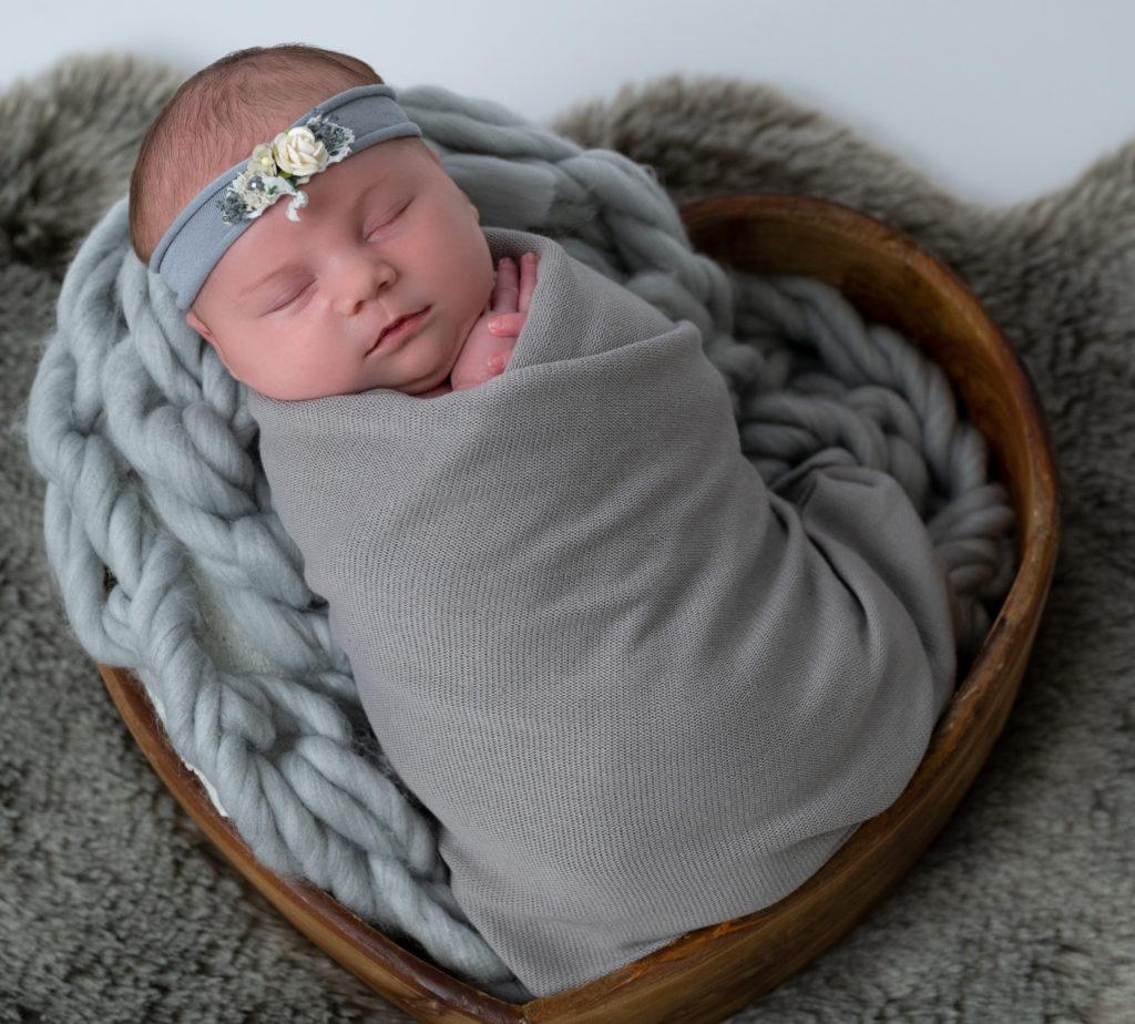 nouvelle née emmaillotée de gris endormie dans un coeur en bois photographe naissance nouveau-né Houilles Yvelines la Défense