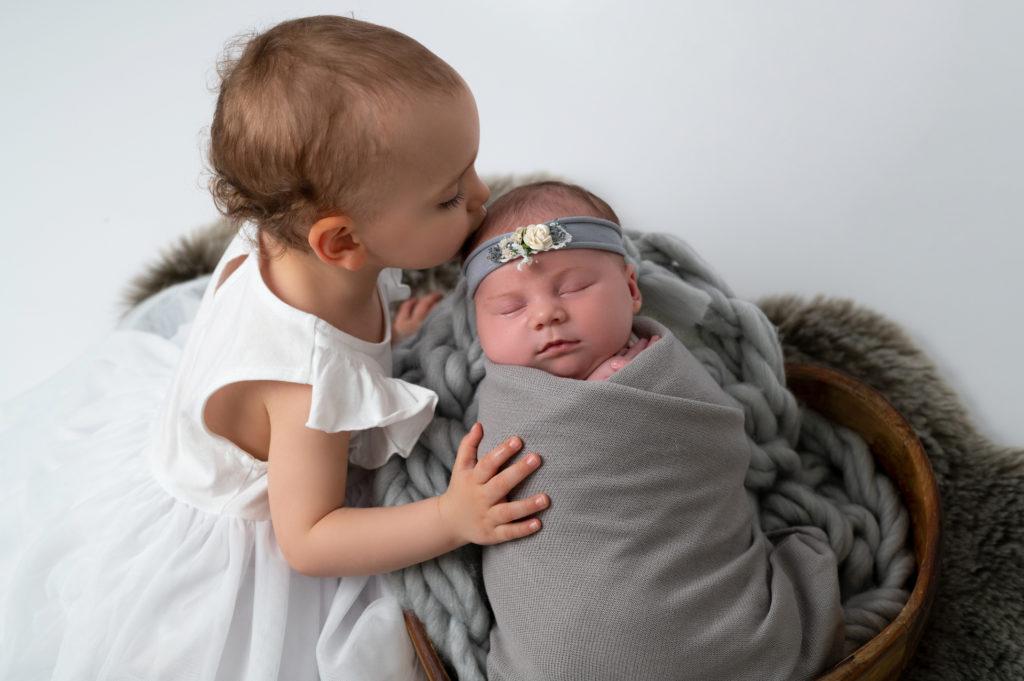 bébé de deux ans faisant un bisou à sa petite soeur nouvelle née emmaillotée de gris endormie dans un coeur en bois photographe naissance nouveau-né Houilles Yvelines la Défense