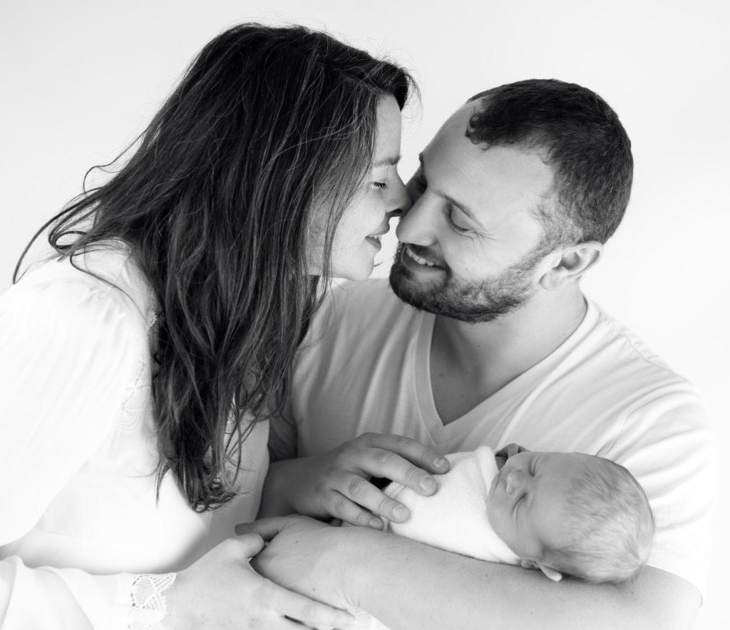 couple de jeunes parents et leur nouveau-né endormi dans leurs bras photographe famille Houilles Yvelines la Défense
