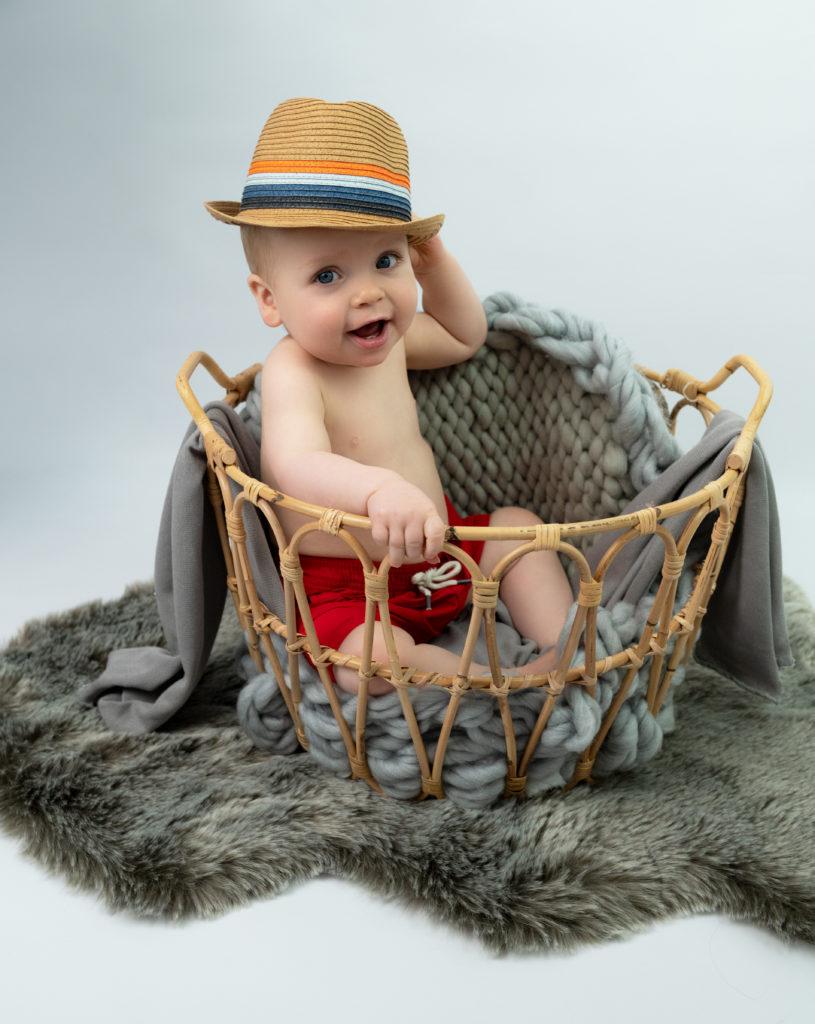 Bébé de 12 mois assis dans un panier chapeau et short rouge photographe bébé famille Houilles Yvelines la Défense