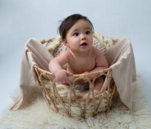 bébé de huit mois dans un panier sur beige tons naturels photographe bébé Houilles Yvelines la Défense