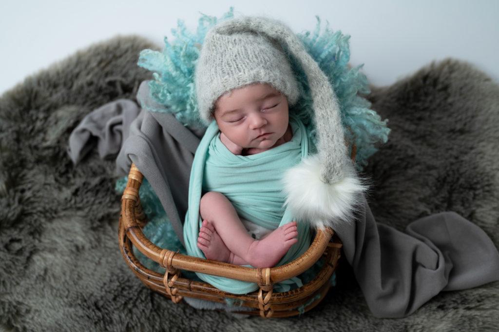 nouveau-né endormi emmailloté de vert menthe dans une caisse en rotin photographe naissance nouveau-né Houilles la Défense