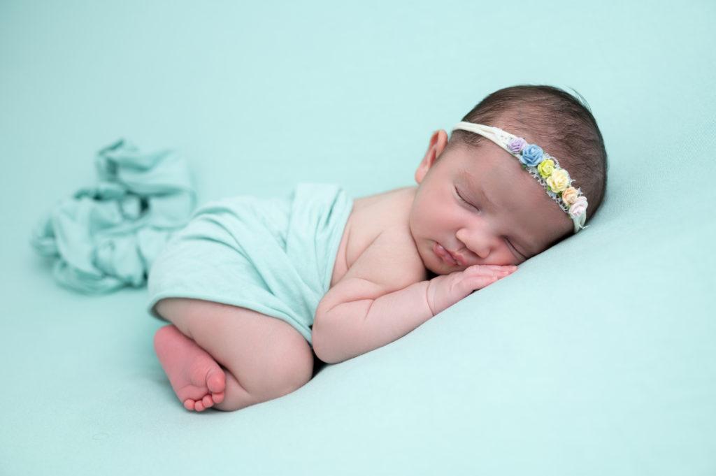 nouvelle-née emmaillotée de vert endormie sur posing bag en pose bumup photographe naissance nouveau-né bébé Houilles Yvelines la Défense