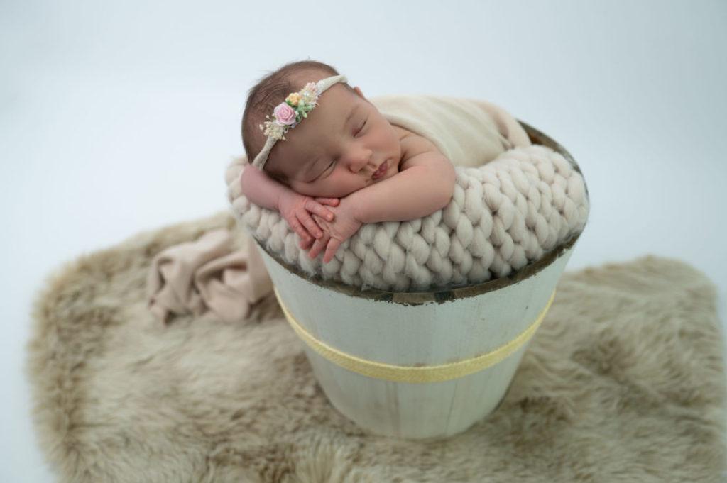 nouvelle-née endormie dans un seau en bois photographe naissance nouveau-né Houilles Yvelines la Défense