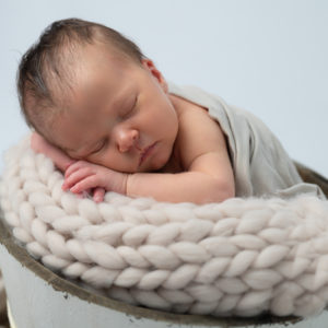 nouveau-né endormi dans un seau en bois le menton sur les mains photographe naissance nouveau-né Houilles Yvelines la Défense
