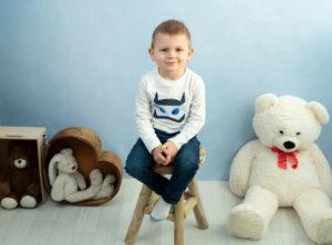 petit garçon sur fond bleu assis sur un tabouret photographe enfant Houilles Yvelines la Défense