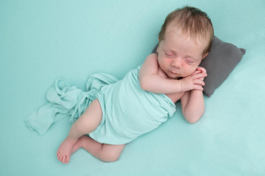nouveau-né endormi en side pose sur beanbag vert menthe photographe naissance nouveau-né Houilles Yvelines la Défense