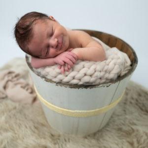 Nouveau-né endormi dans un seau en bois sourire photographe naissance nouveau-né Houilles Yvelines la Défense