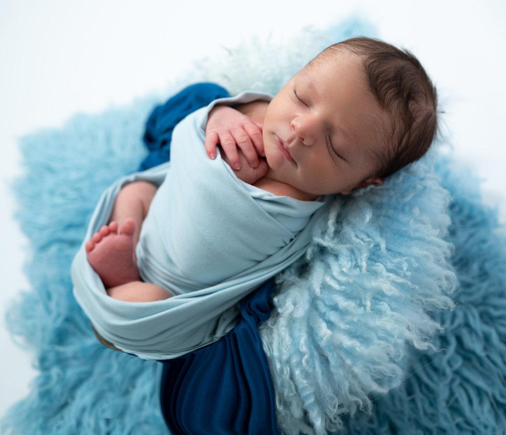 nouveau-né emmailloté de bleu endormi sur fluffy bleu photographe naissance nouveau-né Houilles Yvelines la Défense